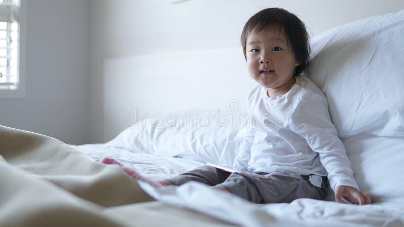 Litet asiatiskt kinesiskt litet barnsammanträde på sängen missbrukade till ipad arkivfoto