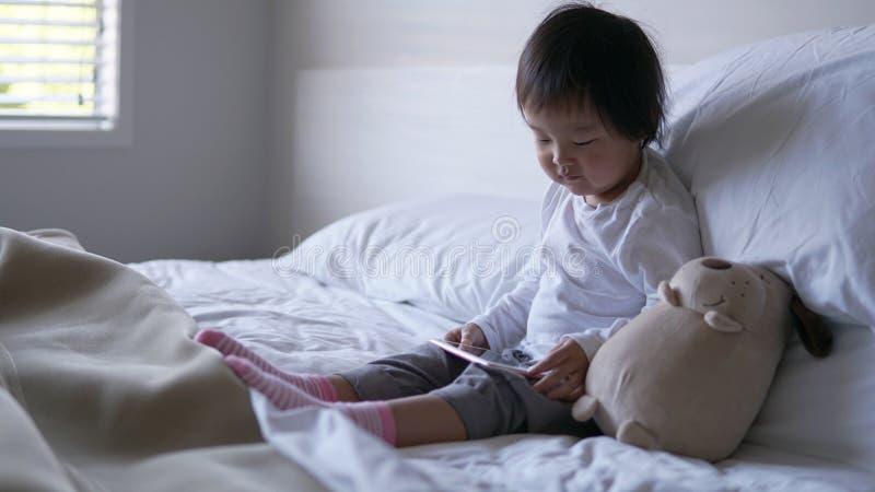 Litet asiatiskt kinesiskt litet barnsammanträde på sängen missbrukade till ipad arkivfoton