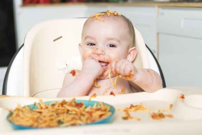 Litet b som äter hennes matställe och gör en röra fotografering för bildbyråer