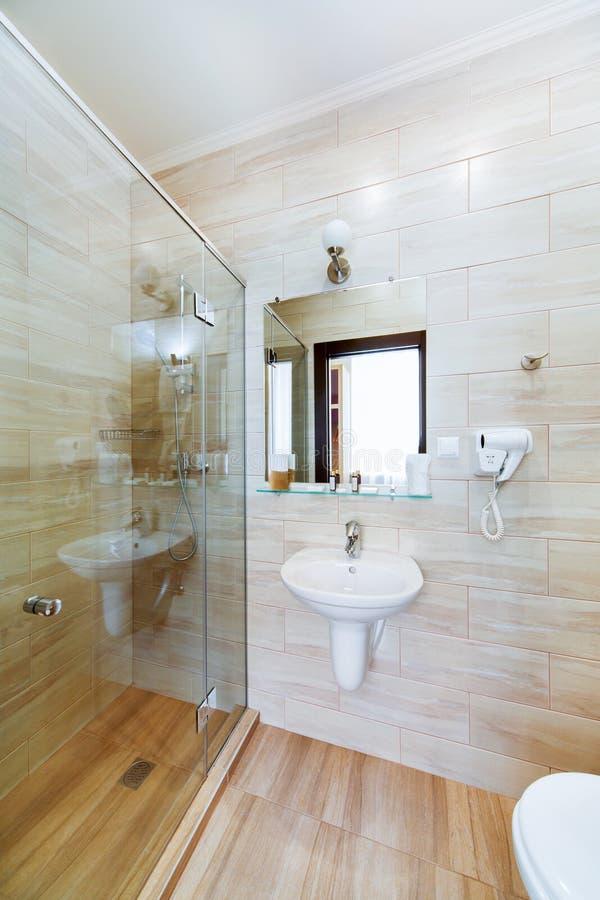 Litet badrum av hotellrummen, med duschen och handfatet arkivbilder
