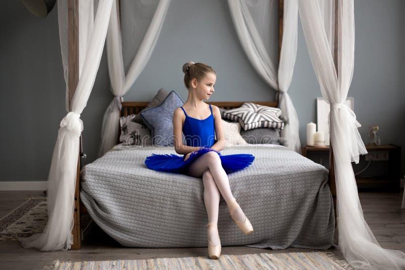 Litet ballerinasammanträde på en säng Gulliga liten flickadrömmar av att bli en ballerina royaltyfri foto