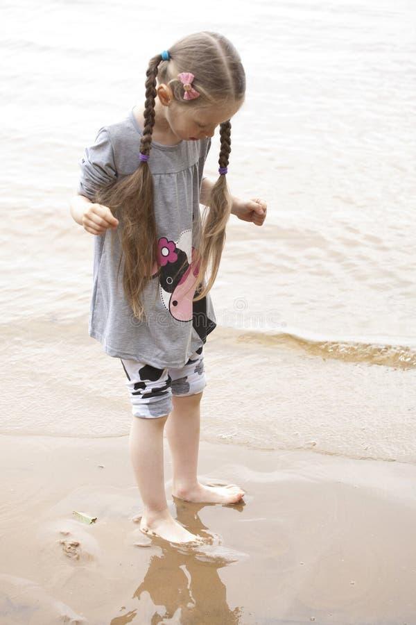 Litet barfota flickaanseende nära floden arkivbilder