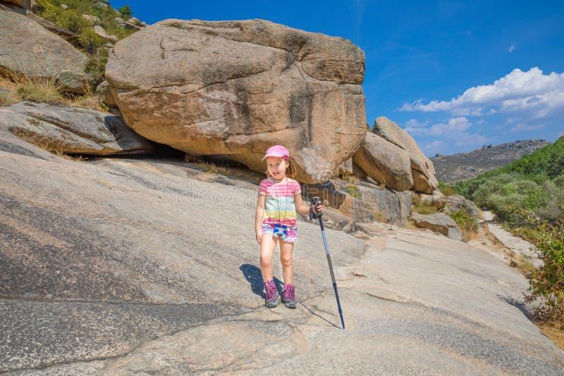 Litet barn för äventyrare med trekking pinnar som hiling i stenigt berg royaltyfri fotografi