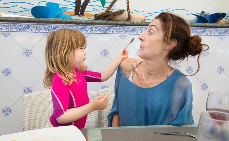 Litet barn för rolig plats som sätter skeden i moderframsida royaltyfri fotografi