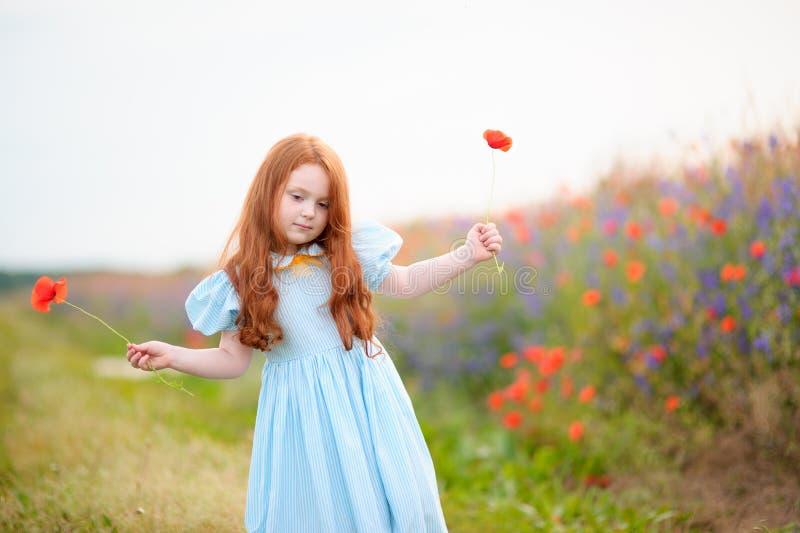 Litet barn för ståenderödhårig man med två lösa blommor på handstaen fotografering för bildbyråer