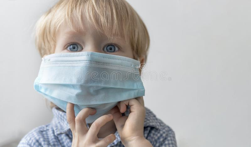Litet barn för unge för Europeanan Caucasian pojkebarn som är blont i blå medicinsk maskering på grå bakgrund Begrepp av den epid arkivfoton
