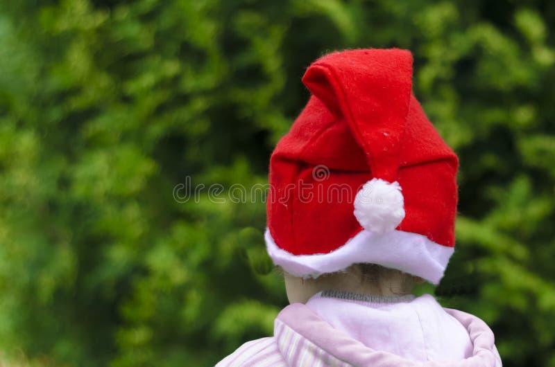 Litet barn i den santa hatten på en grön bakgrund dekorera ett julträd vinter f?r snow f?r pojkeferielay nytt v?ntande ?r arkivbild