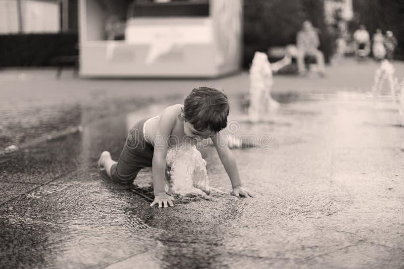 Litet barn i en plaskande vattenspringbrunn royaltyfri bild