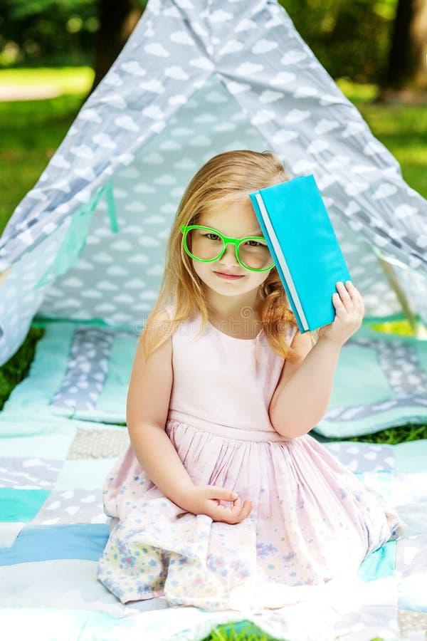 Litet barn i exponeringsglas Flickan har en bok Begreppet av betesmarken royaltyfria bilder