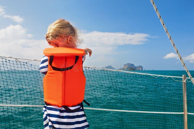 Litet barn i flytväst ombord av segelbåten royaltyfria foton