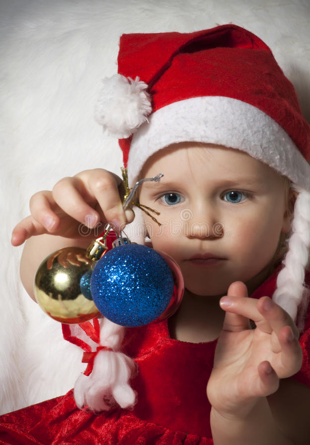 Litet barn i julhatt med garneringar för julträd royaltyfri fotografi