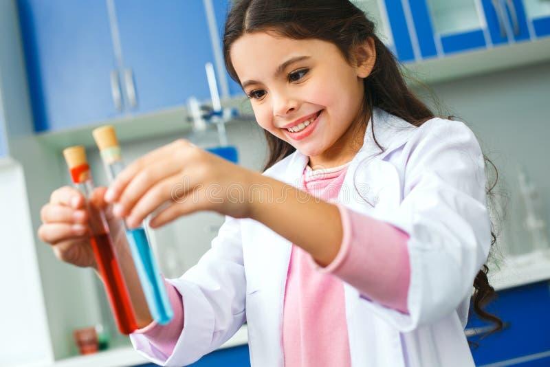 Litet barn med att lära grupp i skolalaboratoriumet som jämför två flytande royaltyfri bild