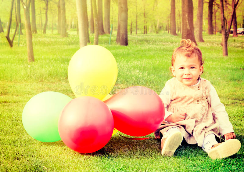 Litet barn med ballonger arkivbild