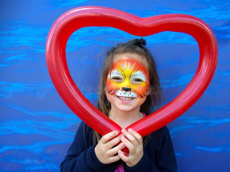 Litet barn med lejonframsidamålning fotografering för bildbyråer