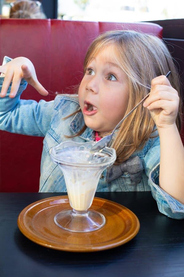 Litet barn med roligt framsidauttryck som äter vaniljglass från kristallkoppen i restaurang arkivfoto