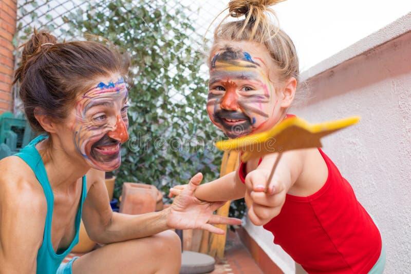 Litet barn med trollspöet och kvinnan med den målade framsidan arkivfoto