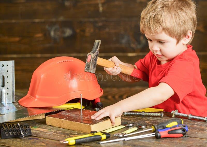 Litet barn på upptagna framsidalekar med hammarehjälpmedlet hemma i seminarium Handcrafting begrepp Ungepojkelek som faktotum bar fotografering för bildbyråer