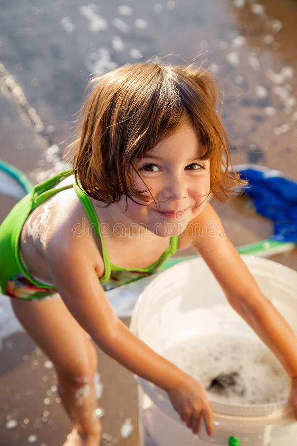 Litet barn som är lyckligt att hjälpa att tvätta bilen royaltyfria foton