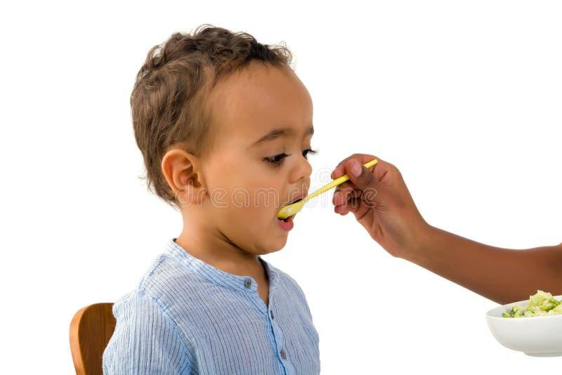 Litet barn som äter grönsaker arkivfoton