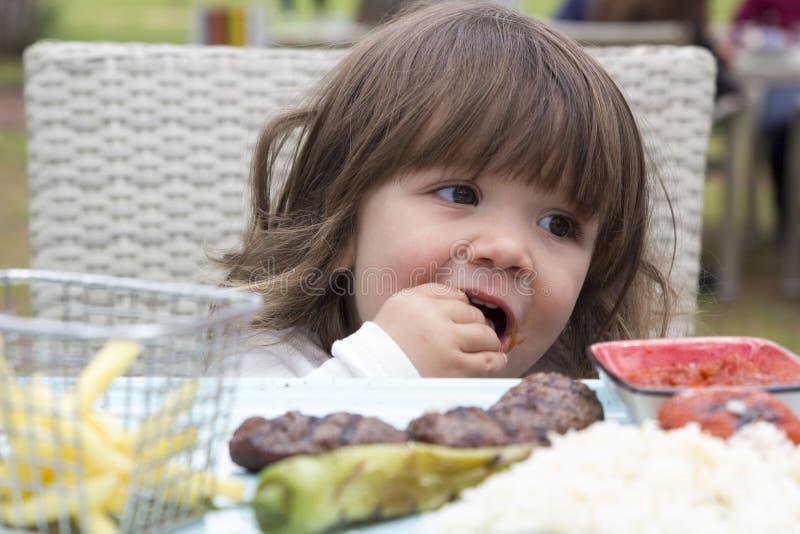 Litet barn som äter mat på hennes egna fotografering för bildbyråer