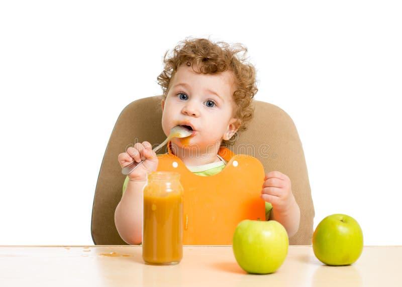 Litet barn som äter puré med skedsammanträde på royaltyfri foto