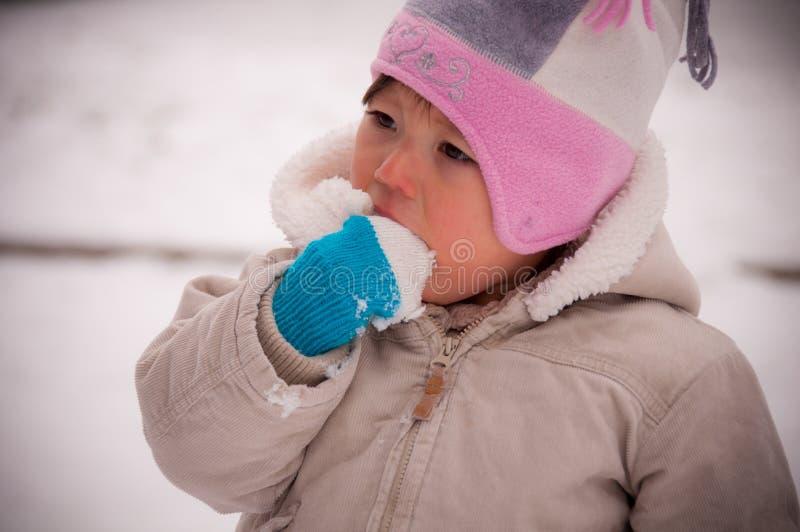 Litet barn som äter Snow arkivbilder