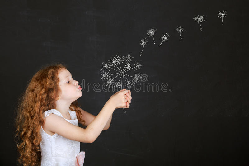 Litet barn som blåser maskrosen med teckningen i svart tavla royaltyfria bilder