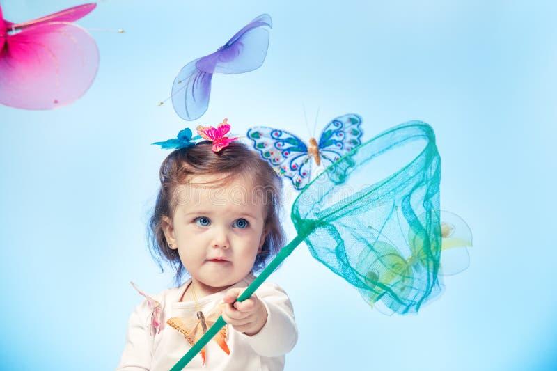 Litet barn som fångar fjärilar arkivbilder