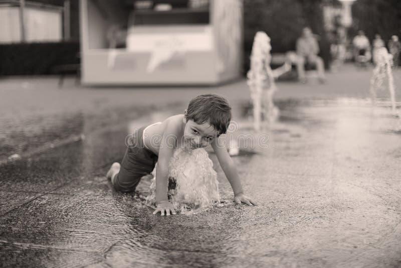 Litet barn som går i en plaskande vattenspringbrunn arkivfoton