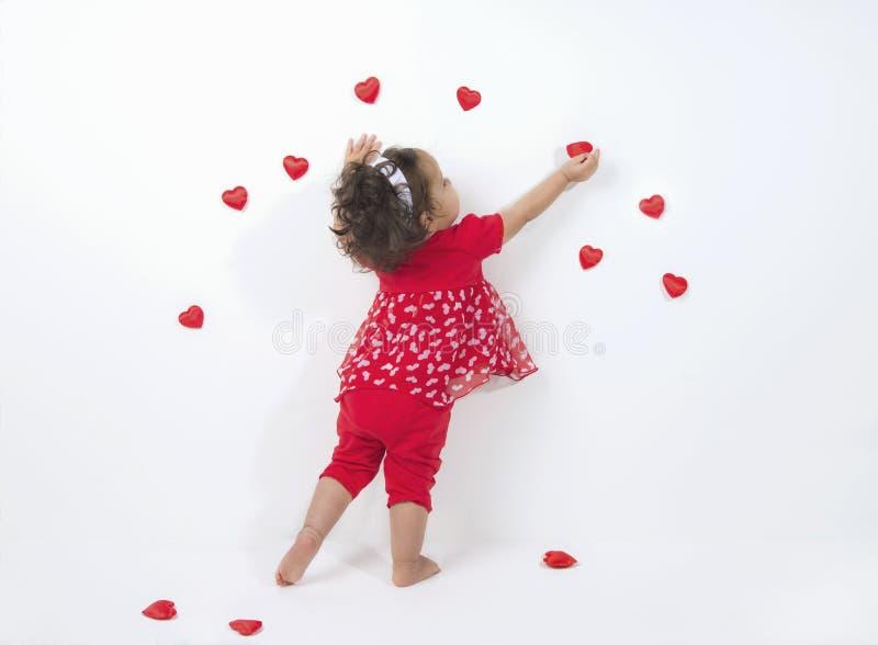 Litet barn som hänger röda hjärtor för ferie arkivbilder