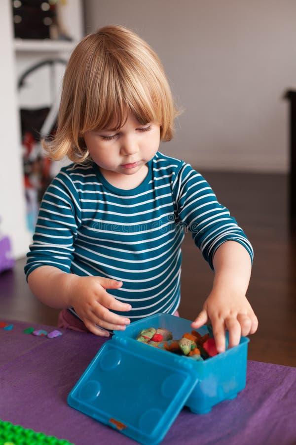 Litet barn som lagrar plasticine i ask royaltyfria foton