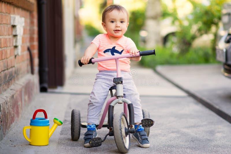 Litet barn som sitter på en rosa trehjuling på en asfaltgrov asfaltbeläggningtrottoar arkivbilder