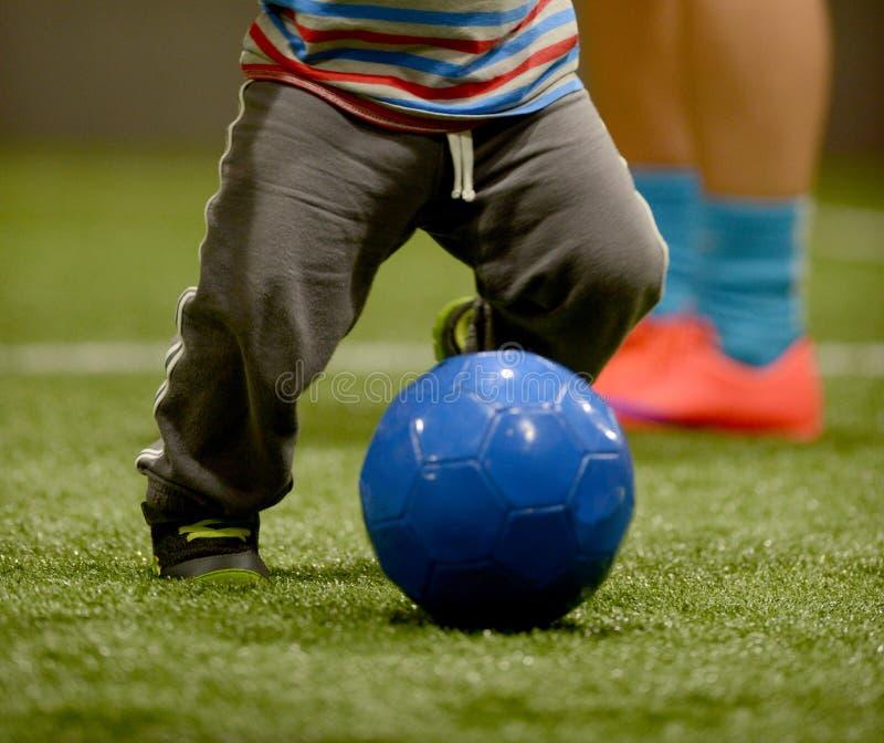 Litet barn som spelar fotboll arkivbilder
