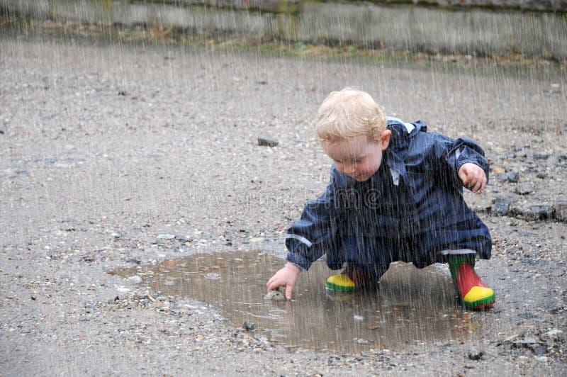 Litet barn som spelar i en pöl
