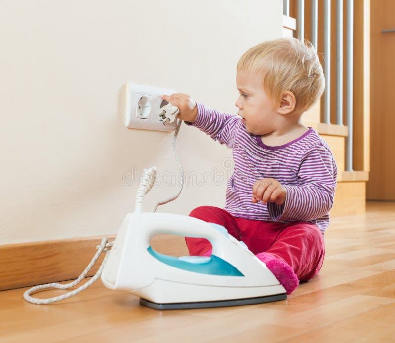 Litet barn som spelar med elektriskt järn arkivbilder