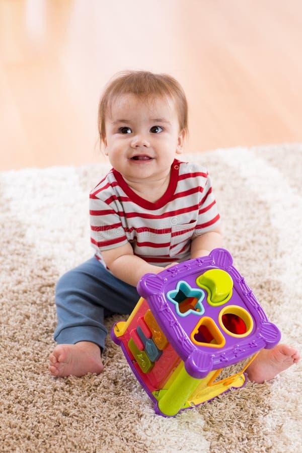 Litet barn som spelar med en formsorterare arkivfoto