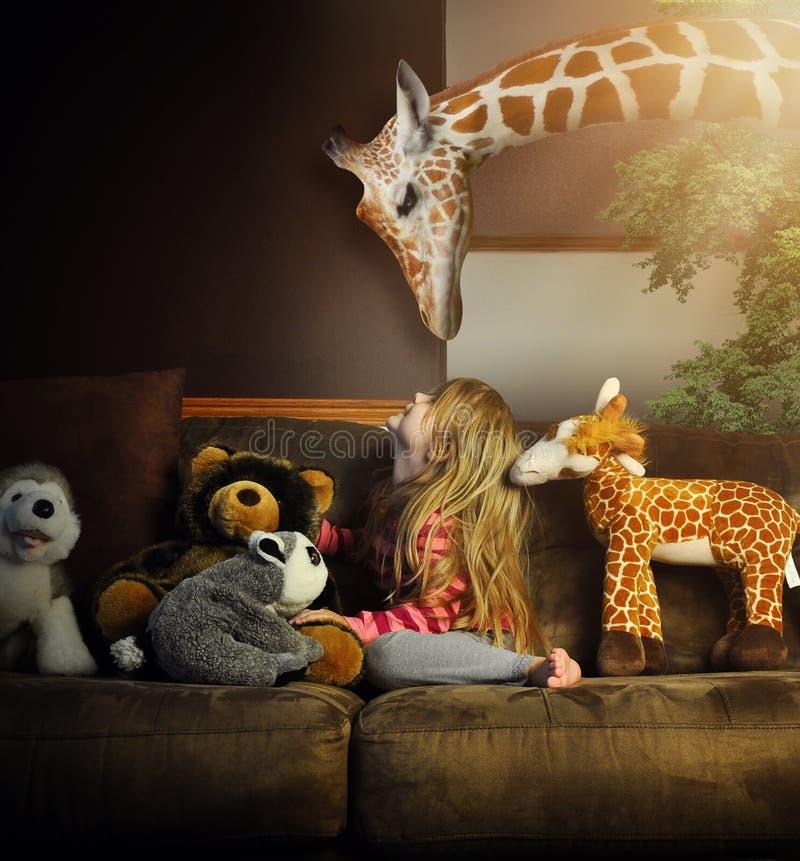 Litet barn som spelar med giraffet i hus arkivfoton