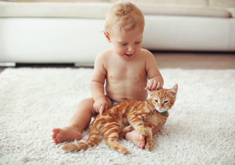 Litet barn som spelar med katten royaltyfria bilder