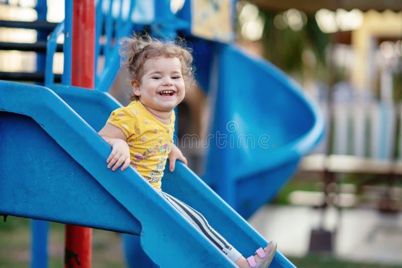 Litet litet barn som spelar på lekplatsdet fria i sommar arkivbilder