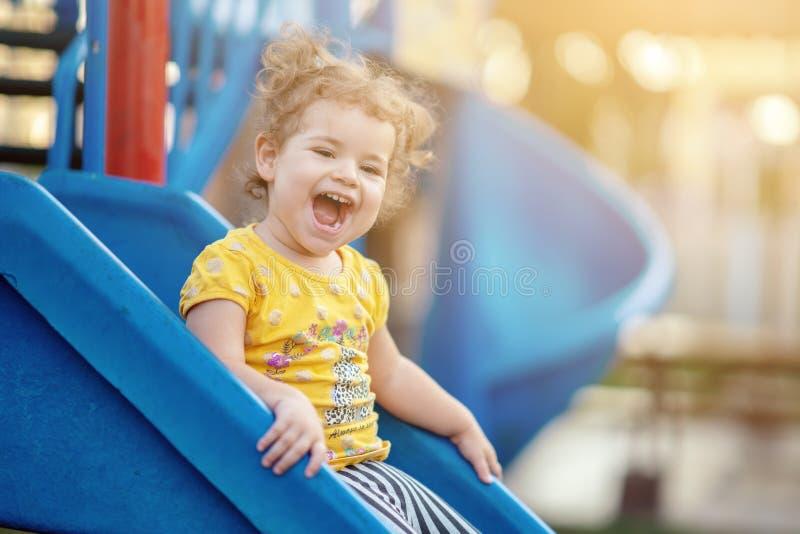 Litet litet barn som spelar på lekplatsdet fria i sommar arkivbild