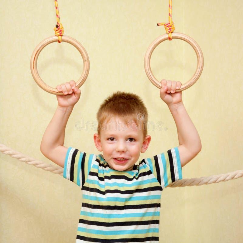 Litet barn som spelar sportar på gymnastiska cirklar royaltyfri foto
