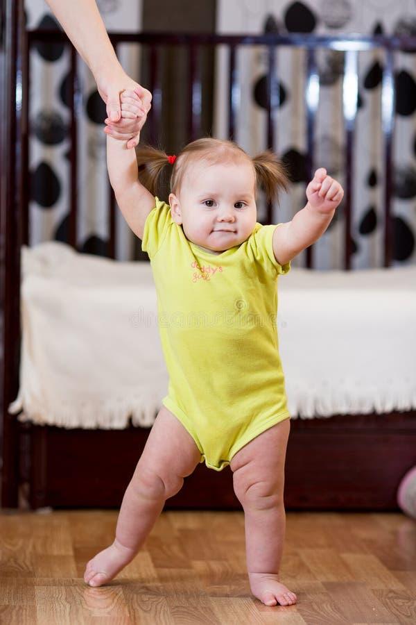 Litet barn som tar första steg med moderhjälp fotografering för bildbyråer