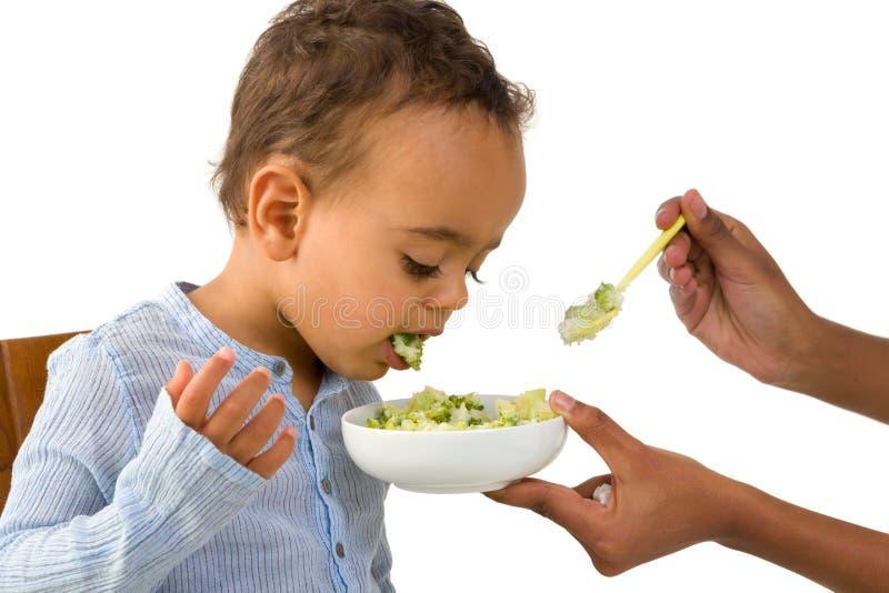 Litet barn som ut spottar hans grönsaker arkivbild