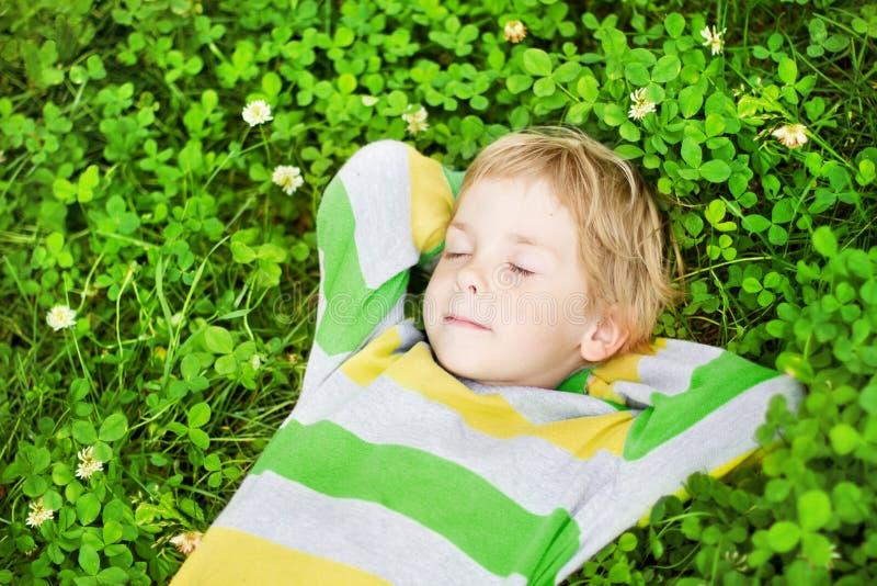 Litet barn som utomhus sovar på gräs royaltyfria bilder