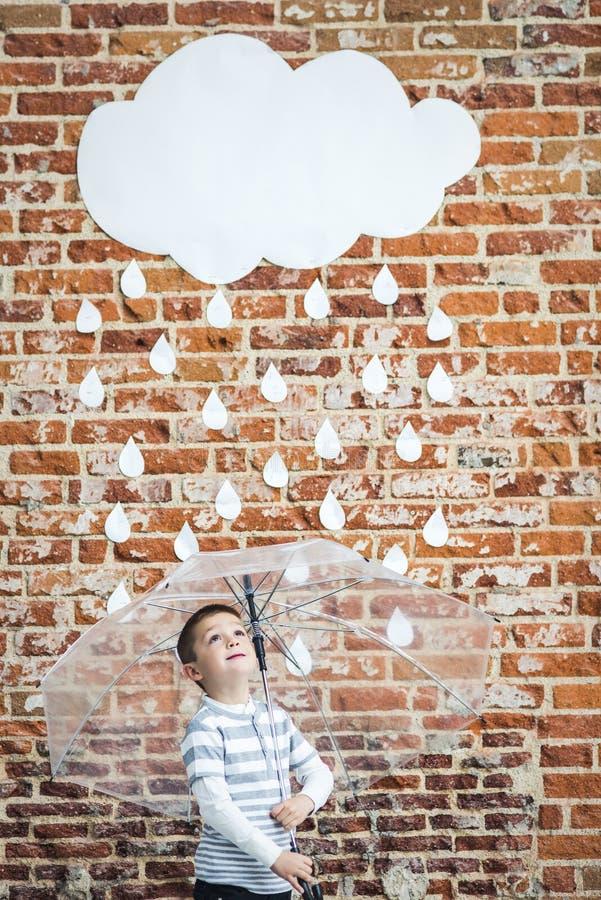 Litet barn under vita pappregndroppar arkivbilder