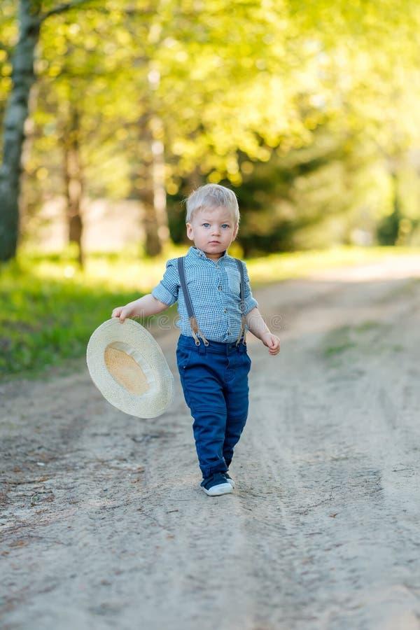 Litet barnbarn utomhus Den lantliga platsen med en som är årig, behandla som ett barn pojken med sugrörhatten arkivbilder