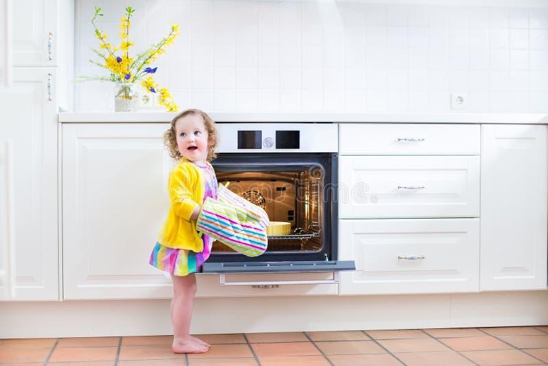 Litet barnflicka i köktumvanten bredvid ugnen med äppelpajen royaltyfri fotografi