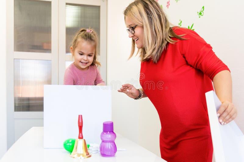 Litet barnflicka i perioden f?r yrkes- terapi f?r barn som g?r sensoriska sk?mtsamma ?vningar med hennes terapeut fotografering för bildbyråer