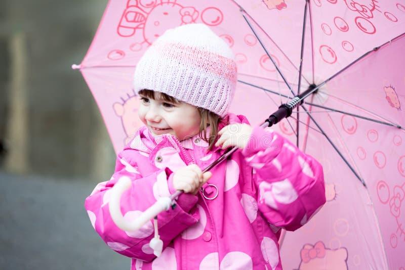 Litet barnflicka med det rosa paraplyet arkivfoton