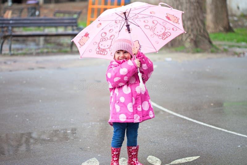 Litet barnflicka med det rosa paraplyet arkivbilder